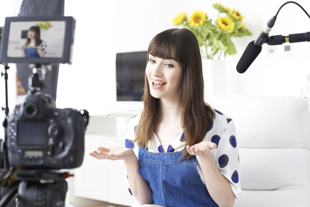 Photo of woman in front of camera taping a segment